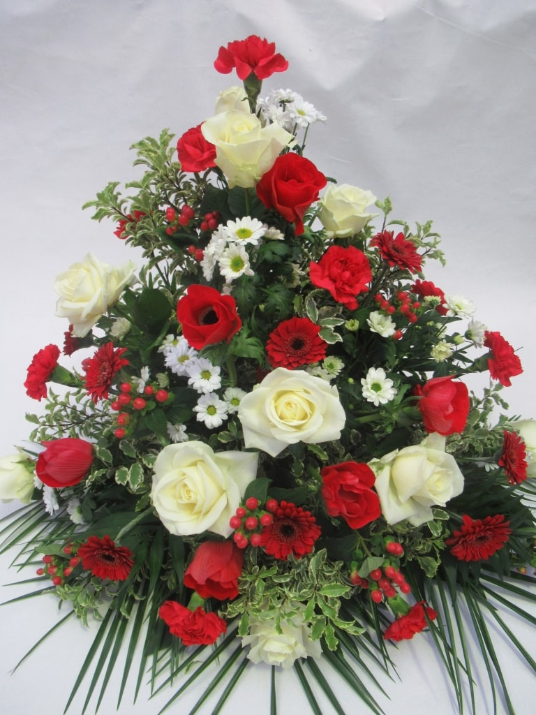Trauergesteck 1: Rot und Weiß | Trauergestecke in Rot und Weiß gehören zu den Klassikern der Trauerfloristik. Sie sind ebenso stilvoll wie wandlungsfähig. Je nach Saison lassen sich weiße und rote Rosen und Gerbera mit Anemonen, Nelken, Hypericum und vielen anderen Blüten kombinieren.